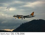 Купить «Airbus Tigerair flies in a storm», фото № 30178094, снято 29 ноября 2016 г. (c) Игорь Жоров / Фотобанк Лори