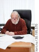 Купить «Пожилой мужчина инженер на рабочем месте среди чертежей, портрет», фото № 30195570, снято 22 февраля 2019 г. (c) Кекяляйнен Андрей / Фотобанк Лори