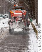 Купить «Трактор разбрасывает на тротуаре твердый реагент для таяния снега. Уборка московских улиц зимой», фото № 30195906, снято 21 февраля 2019 г. (c) Наталья Николаева / Фотобанк Лори