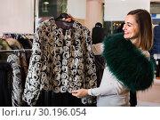 Купить «Woman choosing patterned fur jacket in women's cloths store», фото № 30196054, снято 26 марта 2019 г. (c) Яков Филимонов / Фотобанк Лори
