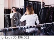 Купить «Smiling girl deciding on warm sheepskin coat», фото № 30196062, снято 26 марта 2019 г. (c) Яков Филимонов / Фотобанк Лори