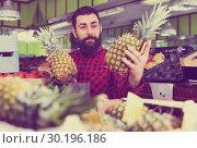 Купить «Young male seller offering pineapples», фото № 30196186, снято 15 ноября 2016 г. (c) Яков Филимонов / Фотобанк Лори