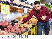 Купить «Young male seller offering potatoes», фото № 30196194, снято 15 ноября 2016 г. (c) Яков Филимонов / Фотобанк Лори