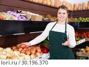 Купить «female seller in apron offering fresh greens and vegetables», фото № 30196370, снято 18 июля 2019 г. (c) Яков Филимонов / Фотобанк Лори