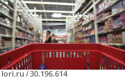 Купить «Grocery Cart Rolls Along Rows With Blurry Children's Toys», видеоролик № 30196614, снято 3 октября 2018 г. (c) Pavel Biryukov / Фотобанк Лори