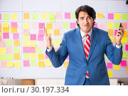 Купить «Young handsome employee with many conflicting priorities», фото № 30197334, снято 16 октября 2018 г. (c) Elnur / Фотобанк Лори