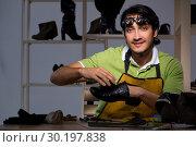Купить «Young shoemaker in workshop at night», фото № 30197838, снято 24 октября 2018 г. (c) Elnur / Фотобанк Лори