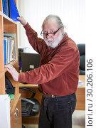 Купить «Пожилой мужчина в очках и с седой бородой стоит у шкафа с документами», фото № 30206106, снято 22 февраля 2019 г. (c) Кекяляйнен Андрей / Фотобанк Лори