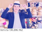 Купить «portrait of young guy try on bucket hat at store», фото № 30206162, снято 2 мая 2017 г. (c) Яков Филимонов / Фотобанк Лори