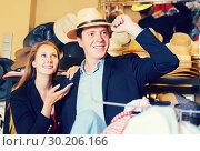 Купить «happy female and man choosing hats in the store», фото № 30206166, снято 2 мая 2017 г. (c) Яков Филимонов / Фотобанк Лори