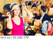 Купить «adult smiling woman try on boater hat in shopping mall», фото № 30206170, снято 2 мая 2017 г. (c) Яков Филимонов / Фотобанк Лори