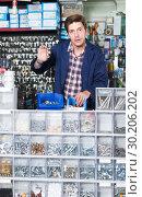 Купить «Man standing near the counter and selling details for plumbing in hardware shop», фото № 30206202, снято 4 мая 2017 г. (c) Яков Филимонов / Фотобанк Лори