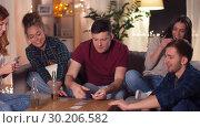 Купить «friends playing cards game at home in evening», видеоролик № 30206582, снято 12 января 2019 г. (c) Syda Productions / Фотобанк Лори