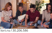 Купить «friends playing cards game at home in evening», видеоролик № 30206586, снято 12 января 2019 г. (c) Syda Productions / Фотобанк Лори