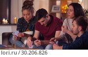 Купить «friends playing cards game at home in evening», видеоролик № 30206826, снято 12 января 2019 г. (c) Syda Productions / Фотобанк Лори