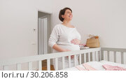 Купить «happy pregnant woman touching her belly at home», видеоролик № 30206858, снято 18 февраля 2019 г. (c) Syda Productions / Фотобанк Лори