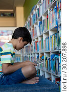 Купить «Schoolboy using digital tablet on sofa in library», фото № 30207898, снято 10 ноября 2018 г. (c) Wavebreak Media / Фотобанк Лори