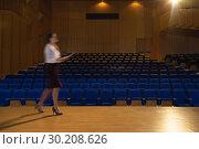 Купить «Businesswoman practicing and learning script while walking in the auditorium», фото № 30208626, снято 15 ноября 2018 г. (c) Wavebreak Media / Фотобанк Лори