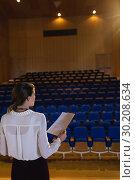 Купить «Businesswoman practicing and learning script while standing in the auditorium», фото № 30208634, снято 15 ноября 2018 г. (c) Wavebreak Media / Фотобанк Лори