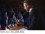 Купить « Businessman holding podium speaker in his hand at auditorium», фото № 30208802, снято 15 ноября 2018 г. (c) Wavebreak Media / Фотобанк Лори