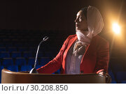 Купить «Businesswoman looking and thinking while standing on stage in auditorium», фото № 30208850, снято 15 ноября 2018 г. (c) Wavebreak Media / Фотобанк Лори