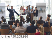 Купить «Businessman standing at podium with colleagues and speaks in a business seminar», фото № 30208986, снято 21 ноября 2018 г. (c) Wavebreak Media / Фотобанк Лори