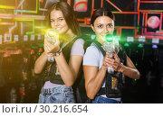 Купить «Girl took aim and holding guns during laser tag game in dark lab», фото № 30216654, снято 23 августа 2018 г. (c) Яков Филимонов / Фотобанк Лори