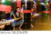 Купить «people with laser guns having fun together in dark labyrinth», фото № 30216670, снято 23 августа 2018 г. (c) Яков Филимонов / Фотобанк Лори