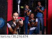 Купить «Portrait of young girl took aim colored laser guns during laser tag game in labyrinth», фото № 30216674, снято 23 августа 2018 г. (c) Яков Филимонов / Фотобанк Лори