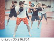 Купить «Young people practicing boxing punches», фото № 30216854, снято 5 мая 2017 г. (c) Яков Филимонов / Фотобанк Лори