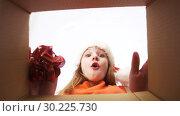 Купить «happy girl in santa hat opening christmas gift», видеоролик № 30225730, снято 27 февраля 2019 г. (c) Syda Productions / Фотобанк Лори