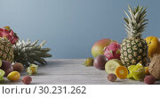 Summer healthy exotic passion fruits, pine apples and dragon fruit on a gray wooden table on a blue. Vegetarian healthy concept. Dolly out motion, 4K video, 3840, 2160p. Стоковое видео, видеограф Ярослав Данильченко / Фотобанк Лори