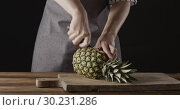 Woman chef's hands are cutting fresh natural pineapple on two halves on a wooden board on a kitchen table on a black background. Motion, 4K UHD video, 3840, 2160p. Стоковое видео, видеограф Ярослав Данильченко / Фотобанк Лори