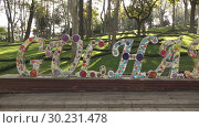 Купить «Big concrete colorful letters GULHANE in a serene city park on a background of green trees in Istanbul Turkey. Panoramic slow motion, Full HD video, 240fps, 1080p.», видеоролик № 30231478, снято 29 ноября 2017 г. (c) Ярослав Данильченко / Фотобанк Лори