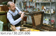 Купить «Professional young man carpenter repairing antique furniture in workshop», видеоролик № 30231606, снято 29 ноября 2018 г. (c) Яков Филимонов / Фотобанк Лори