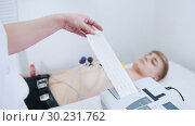 Купить «A medical clinic. A young man receiving a ECG procedure. A results tape coming out of machine», видеоролик № 30231762, снято 14 июля 2020 г. (c) Константин Шишкин / Фотобанк Лори