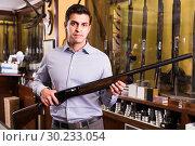Happy male hunter choosing shotgun in store. Стоковое фото, фотограф Яков Филимонов / Фотобанк Лори