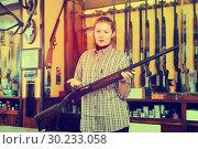 Купить «Attractive salesgirl showing shotgun in store», фото № 30233058, снято 11 декабря 2017 г. (c) Яков Филимонов / Фотобанк Лори