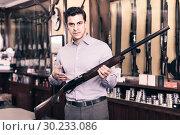 Купить «Handsome adult male in hunting shop with rifle in hands», фото № 30233086, снято 11 декабря 2017 г. (c) Яков Филимонов / Фотобанк Лори