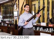 Man owner of hunting shop showing shotgun. Стоковое фото, фотограф Яков Филимонов / Фотобанк Лори