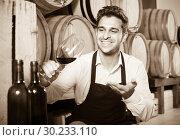 Купить «male seller holding glass on wine in cellar», фото № 30233110, снято 17 июня 2019 г. (c) Яков Филимонов / Фотобанк Лори