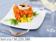 Cube of fresh tartar with salmon, trout, avocado and greens on plate. Стоковое фото, фотограф Яков Филимонов / Фотобанк Лори