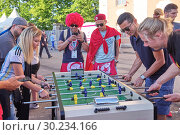 SAINT PETERSBURG, RUSSIA - JUNE 26, 2018: Football fans of the World Cup in the fan zone to play table football in St. Petersburg, Russia. Редакционное фото, фотограф Андрей Зарин / Фотобанк Лори