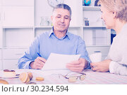 Mature married couple discuss contract and sign important documents. Стоковое фото, фотограф Яков Филимонов / Фотобанк Лори
