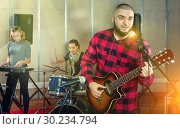 Купить «Guy guitar player and singer practicing with band members in re», фото № 30234794, снято 26 октября 2018 г. (c) Яков Филимонов / Фотобанк Лори