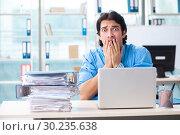 Купить «Handsome businessman unhappy with excessive work in the office», фото № 30235638, снято 19 ноября 2018 г. (c) Elnur / Фотобанк Лори