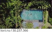 Купить «Brunette girl is swimming in outdoor pool on villa between tropical plants», видеоролик № 30237366, снято 23 января 2019 г. (c) Andriy Bezuglov / Фотобанк Лори