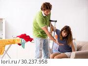 Купить «Husband helping leg injured wife in housework», фото № 30237958, снято 4 октября 2018 г. (c) Elnur / Фотобанк Лори