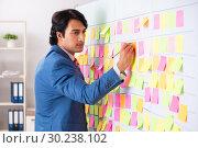 Купить «Young handsome employee with many conflicting priorities», фото № 30238102, снято 16 октября 2018 г. (c) Elnur / Фотобанк Лори
