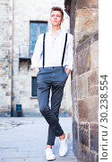 Купить «young European guy in shirt and trousers with suspenders walking around city», фото № 30238554, снято 27 июня 2018 г. (c) Татьяна Яцевич / Фотобанк Лори